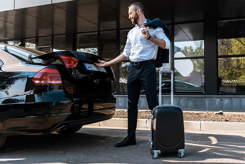 putting luggage into rental car