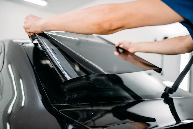 man applying car window tint