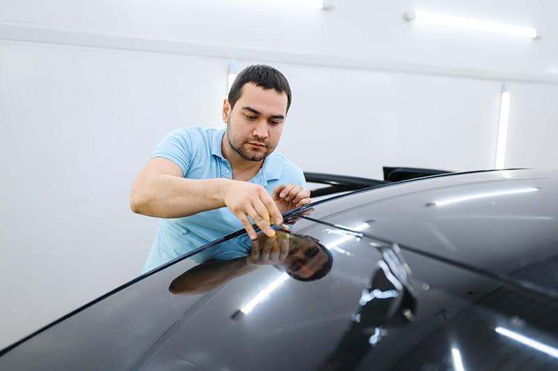 guy cutting car window tint