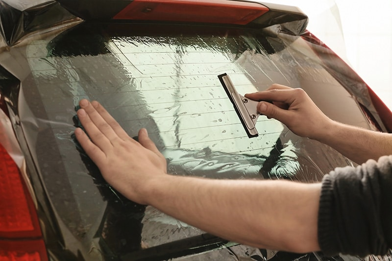 worker applying car window tint